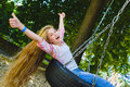 Little girl at playground. Child playing outdoors in summer. Teenager on a swing.