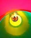 Little girl on the playground comes down to one big tunnel slide colorful Royalty Free Stock Photography