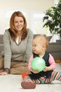 Little girl playing with ball sitting on living room floor mum in background looking happy Stock Photo