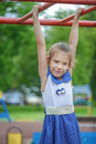 Little girl playing on bar of playground beautiful cheerful Royalty Free Stock Photo