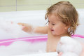 Little girl playing in the bath with foam Stock Image