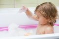 Little girl playing in the bath with foam Royalty Free Stock Photography