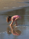 Little girl playing on the beach with her reflection on the water sunshine coast in queensland australia Royalty Free Stock Photo