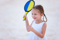 Little girl playing beach tennis on vacation Royalty Free Stock Image