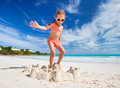 Little girl playing at beach tropical jumping on a sand castle having fun Royalty Free Stock Photo