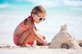 Little girl playing at beach tropical making sand castle Stock Image