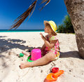 Little girl playing on the beach under palm Royalty Free Stock Image