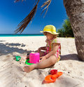 Little girl playing on the beach under palm Royalty Free Stock Photo