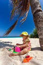 Little girl playing on the beach under palm Royalty Free Stock Images