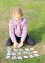 Little girl playing cards in black pants and lila pullover Royalty Free Stock Photo