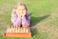 Little girl playing chess in lila pullover wooden Stock Photography