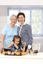 Little girl playing cooking cute mother and grandmother standing behind Royalty Free Stock Images