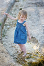 Little girl playing in a creek Stock Photos