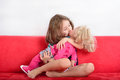 Little girl playing with a doll cute kissing while Stock Photography