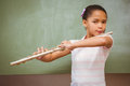 Little girl playing flute in classroom portrait of cute Stock Images
