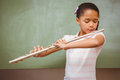 Little girl playing flute in classroom portrait of cute Stock Photo