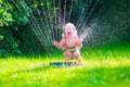 Little girl playing with garden water sprinkler child kid in bathing suit running and jumping kids gardening summer outdoor fun Royalty Free Stock Images