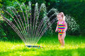 Little girl playing with garden water sprinkler child kid in bathing suit running and jumping kids gardening summer outdoor fun Stock Photography