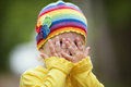 Little girl with playing hide and seek rainbow hat is Stock Images