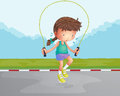 A little girl playing jumping rope at the road illustration of Royalty Free Stock Photo