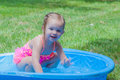 Little girl playing in a kiddie pool wearing pink bathing suit Royalty Free Stock Photo