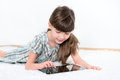 Little girl playing modern digital tablet lying white carpet white room Royalty Free Stock Photography