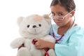 Little girl playing nurse to injured teddy Stock Photos