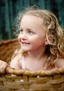 Little girl playing outside hiding wooden basket Stock Photos