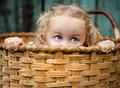 Little girl playing outside hiding wooden basket Royalty Free Stock Photos