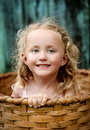 Little girl playing outside hiding wooden basket Stock Photo