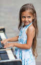 Little girl playing on a piano old black outdoors Stock Photos