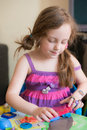 Little girl playing with plasticine at home making different shapes having fun Royalty Free Stock Photo