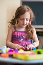 Little girl playing with plasticine at home making faces Stock Photography