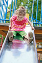 Little girl playing on a playground slide. Royalty Free Stock Photography