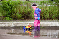 Little girl playing in the puddle Royalty Free Stock Photo