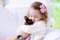 Little girl playing with a real pet rabbit child kids play pets holding bunny children and animals at home or preschool cute Royalty Free Stock Photography