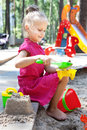 Little girl playing on a sandbox happy playground in the park Royalty Free Stock Photos