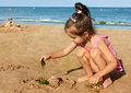Little girl playing on the seaside Stock Image