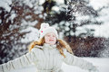 Little girl playing with snow. Falling snow around the child. Royalty Free Stock Photo