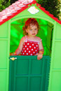 Little girl playing in toy house in the garden inside plastic summer Royalty Free Stock Photo