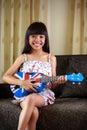 Little girl playing ukulele asian Royalty Free Stock Image