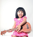 Little girl playing ukulele Royalty Free Stock Photo