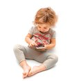 Little girl playing with white smartphone on background Royalty Free Stock Photos