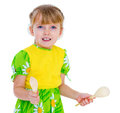 Little girl playing on wooden spoons. Royalty Free Stock Photo