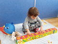The little girl plays with cubes, sitting on a floor