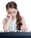 Little girl plays on the electric piano cute serious isolated white Stock Image