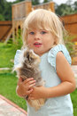 Little girl plays with Guinea pig on meadow Stock Photos