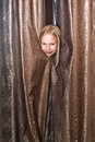 Little girl plays at hide and seek looks out because of curtains Royalty Free Stock Photos