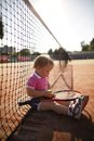 Little girl plays tennis funny outside photo Stock Photo