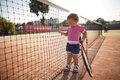 Little girl plays tennis funny outside photo Stock Photos